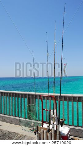 Assortment of fishing poles and tackle on pier with beautiful ocean in distance