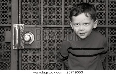 Cute boy standing up against very old screen door