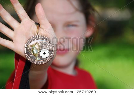 Young soccer playing girl showing off soccer medallion