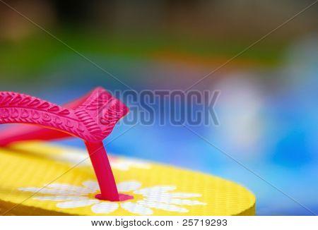 Bright flipflop sandal by backyard pool