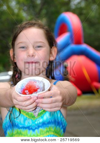 Young girl at fair eating refreshing ice cone