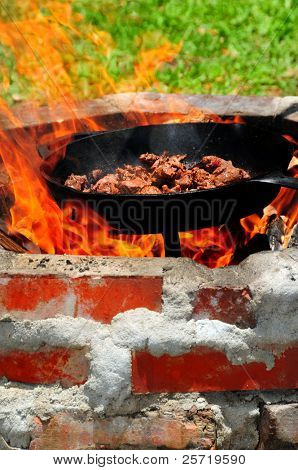 Outdoor brick fire ring with cast iron pot cooking meat