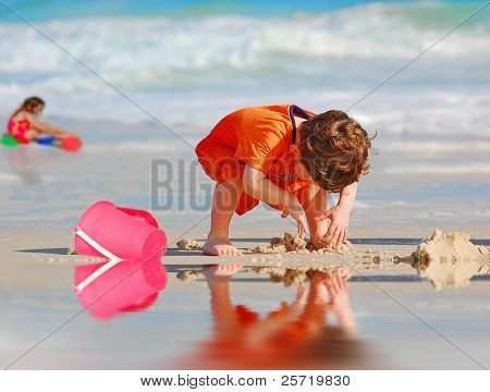 Young boy and girl playing in sand by tidepool at beach