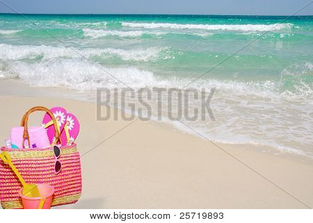 Pretty pink beach bag and accessories on sand by ocean