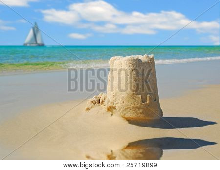 Pretty sandcastle by tidepool with sailboat under pretty sky