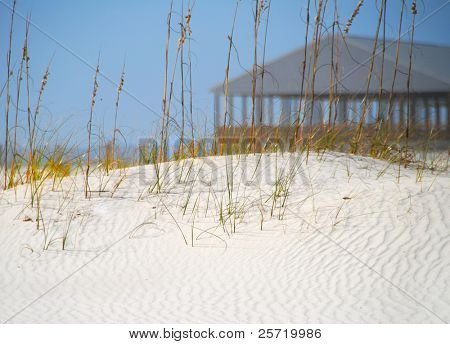 Rippled sand dune with picnic shelter on beach in distance