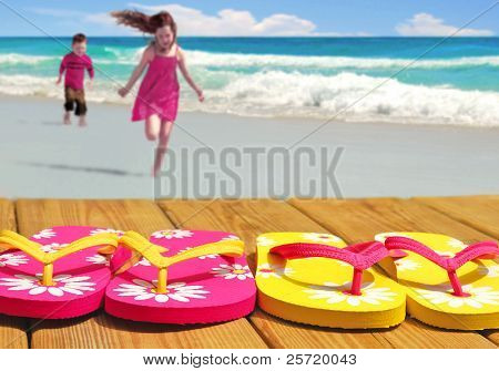 Kids running towards colorful flip flop sandals on boardwalk with ocean in distance