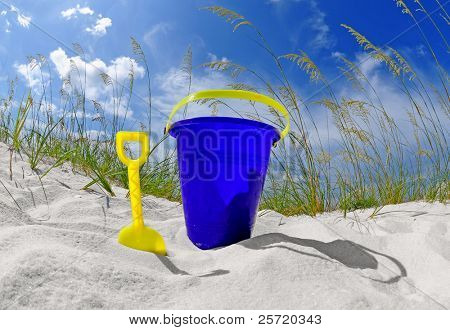 Beach bucket and shovel on beautiful sand dune