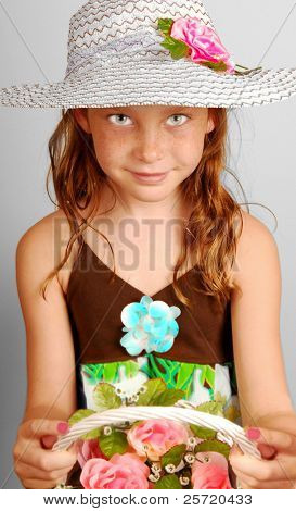 Young girl wearing pretty bonnet holding flower bouquet