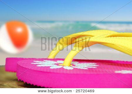 Flip flop sandalen op dok naast beachball en Oceaan roze