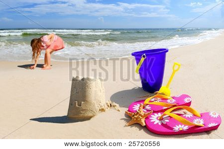 Girl collecting shells by pretty sand castle on seashore by beach accessories