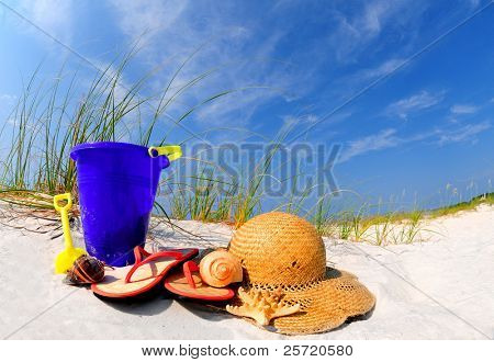 Pretty array of beach accessories on sand dune