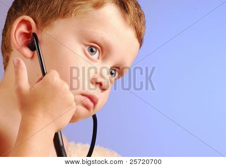 Young boy listening intently through stethoscope