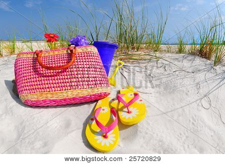 Pretty flipflops and straw bag on coastal beach dune