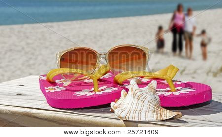 Beach accessories on pier with family walking on beach