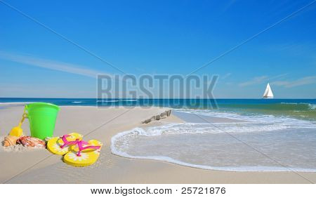 Pretty beach sand toys on dune with gentle waves with sailboat in distance under blue sky