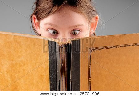Young girl with wide eyes shocked over old book contents