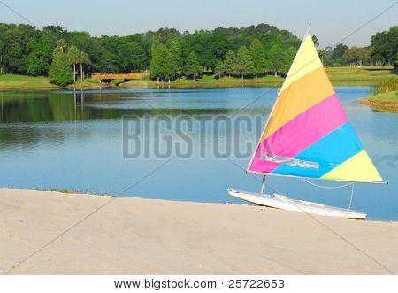pretty sailboat on beach next to still lake
