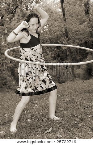 Young girl having fun with hula hoop outside