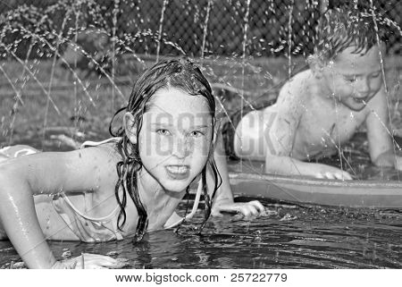 Young boy and girl playing in sprinkler on summer day