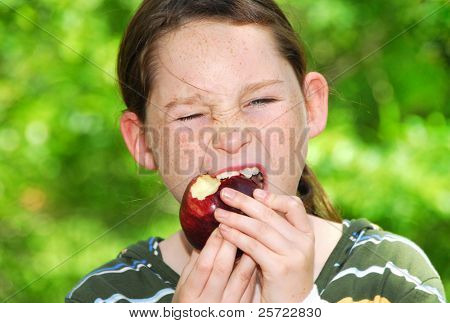 Young girl eating apple outdoors