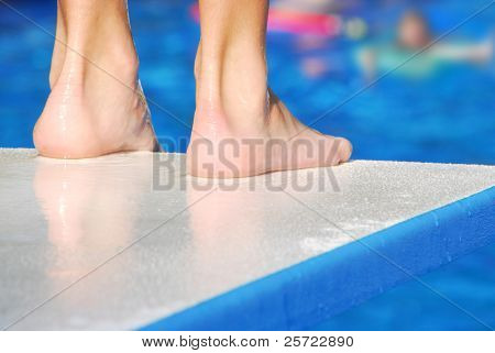 Pair of feet at edge of diving board, waiting for pool to clear before jumping