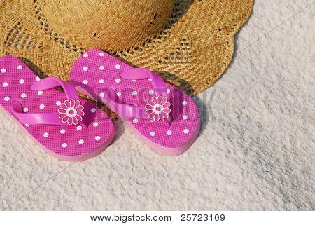 Pretty pink flip flops on beach hat resting on sand
