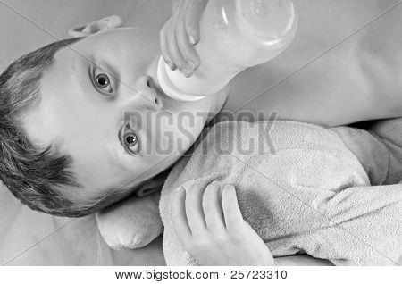 Young toddler ready for nap drinking milk bottle