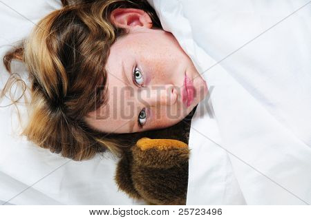 young girl snuggled in covers ready for bed