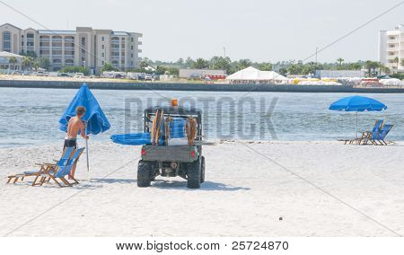 ORANGE BEACH, AL - JUNE 10:  A beach chair vendor removes his umbrella on a beautiful day at Perdido Pass, AL on June 10, 2010 as the BP oil washing ashore drives away customers.