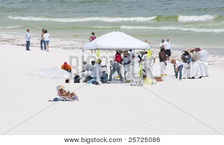 PENSACOLA BEACH - JUNE 23:  An unidentified beachgoer tries to enjoy the beach near BP oil workers on June 23, 2010 in Pensacola Beach, FL.