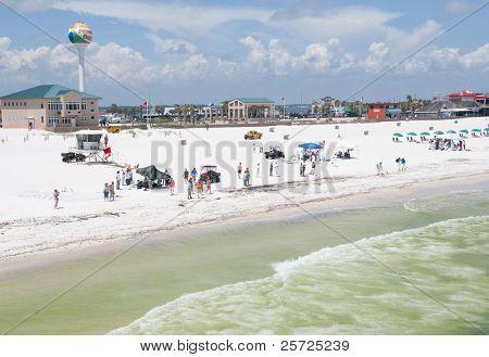 PENSACOLA BEACH - JUNE 23:  BP oil workers and tourists stand on the beach on June 23, 2010 in Pensacola Beach, FL.