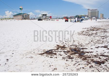 PENSACOLA BEACH - 23 JUNE: Oil lies near the Pensacola Beach, FL pier on June 23, 2010 as tourists stay away from the resort beach at the height of the summer season. BP workers in the distance.