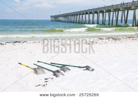 PENSACOLA BEACH - JUNE 23:  BP oil worker shovels lie near large patches of oil washed ashore on deserted Pensacola Beach, FL on June 23, 2010 at the height of the summer tourist season.