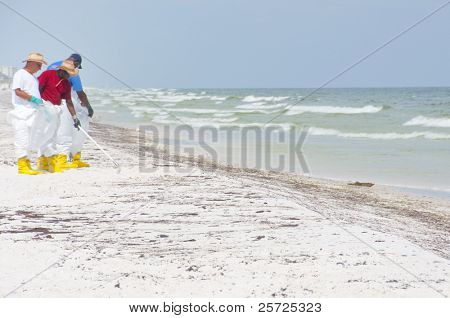 PENSACOLA BEACH - JUNE 23: BP oil workers attempt to clean the beach of oil on June 23, 2010 in Pensacola Beach, FL.