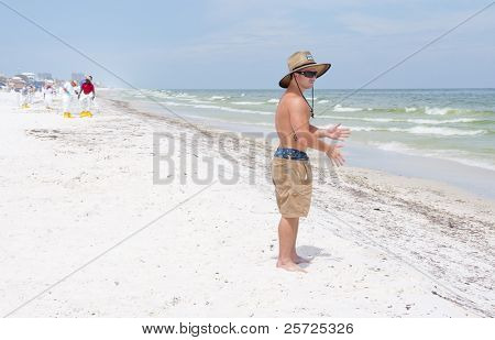 PENSACOLA BEACH - JUNE 23:  An unidentified beachgoer stands on the beach on June 23, 2010 in Pensacola Beach, FL. BP oil workers attempt to clean the beach in the background.
