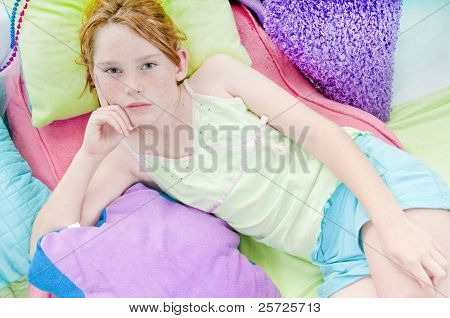 Tweenage girl relaxing on colorful cushions