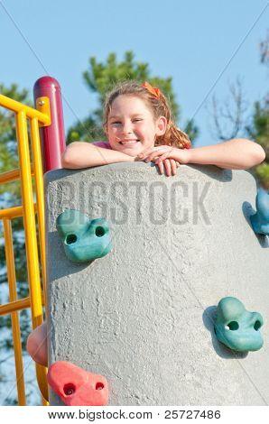 happy girl at top of climbing wall