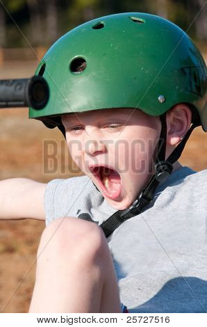 child riding trike wearing helmet