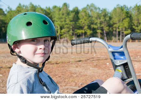 boy riding trike wearing helmet