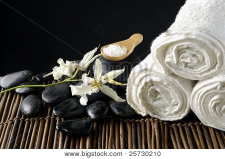 tropical orchid with spa stones and herbal salt in spoon on bamboo mat
