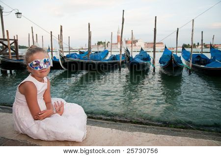 Carnival in Venice, Italy. Portrait of little girl. Gondolas and San Giorgio Maggiore church in background