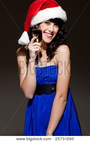 laughing happy woman in santa hat holding glass over dark background