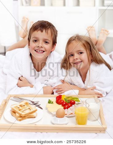 Happy healthy kids having a light breakfast in bed