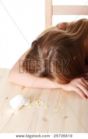 Young woman lying on table full of pills (suicide or drug abuse)