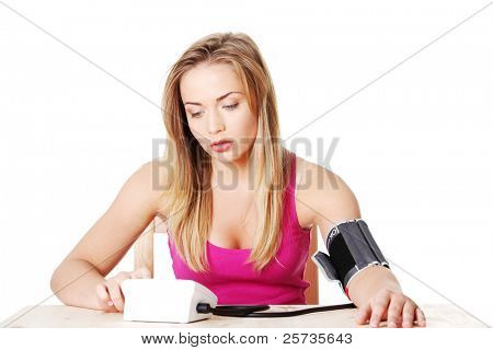 Teen girl checking her blood pressure, over white background