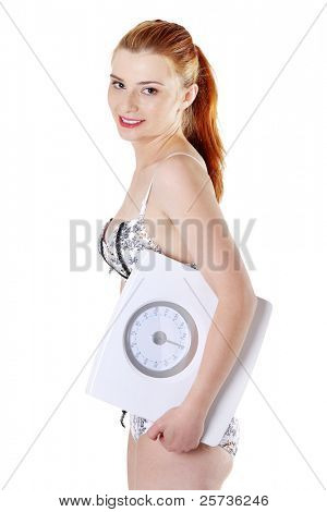 Site view of a young smiling girl holding a scales, isolated on a white background.