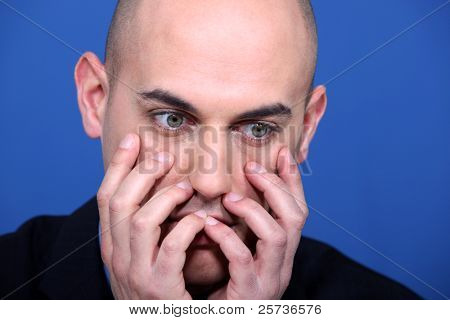 man looking horrified with hands to face