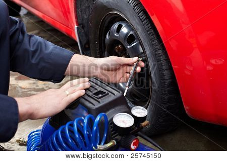 Professional auto mechanic changing a tire. in auto repair shop. Garage.