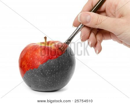 Female hand painting a fresh red apple which is partly black and white and partly colored